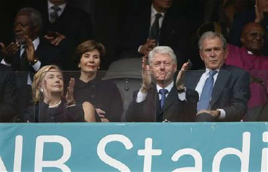 From left, Former U.S. Secretary of State Hillary Rodham Clinton, Laura Bush, Former U.S. President Bill Clinton and Former U.S. President George W. Bush listen Tuesday to speakers during the memorial service for former South African president Nelson Mandela at the FNB Stadium in Soweto near Johannesburg. Photo: AP / AP