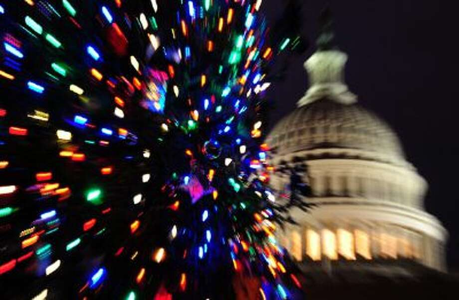 The congressional Christmas tree in front of the Capitol dome. Congress is passing a budget, but leaving many federal benefits behind. Photo: AFP/Getty Images / 2011 AFP