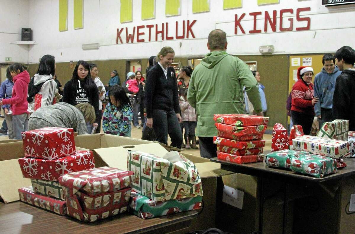 This photo taken Wednesday, Dec. 11, 2013, in Kwethluk, Alaska, shows assistant principal Zach Bastoky (in green kupsuk) waiting to hand out gifts to children after they had their pictures taken with Santa and Mrs. Claus in the school gym. The visit is part of the Alaska National Guard's Operation Santa Claus, which visits several remote Alaska Native villages each year. (AP Photo/Mark Thiessen)