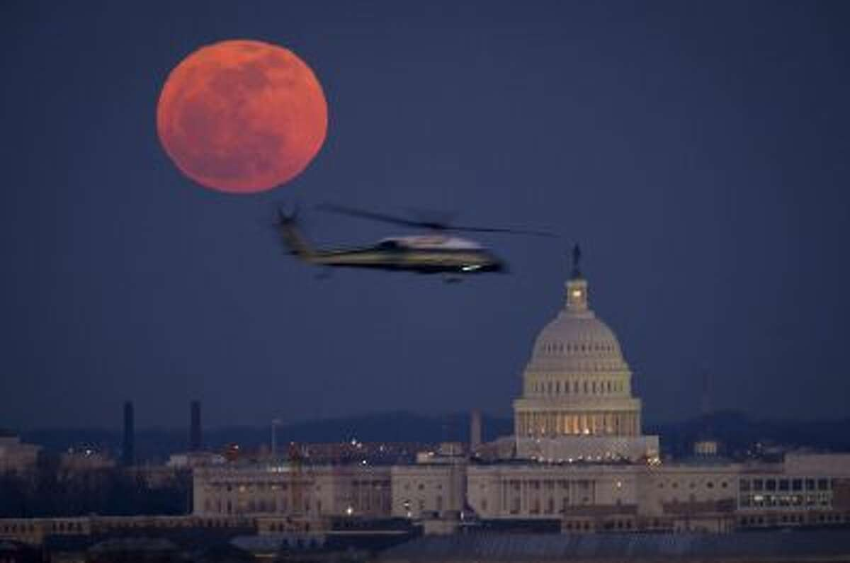 A Marine Corps helicopter flies past a full and the U.S. Capitol in 2012. The Senate was in session all night Wednesday.