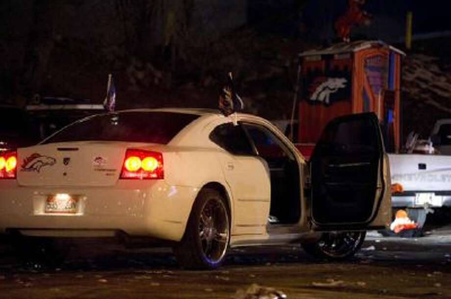 A car sits unattended with its door open inside a crime scene where Denver police say four people were stabbed after a fight broke out following a game between the Denver Broncos and San Diego Chargers in Parking Lot F of Sports Authority Field at Mile High on December 12, 2013, in Denver, Colorado.