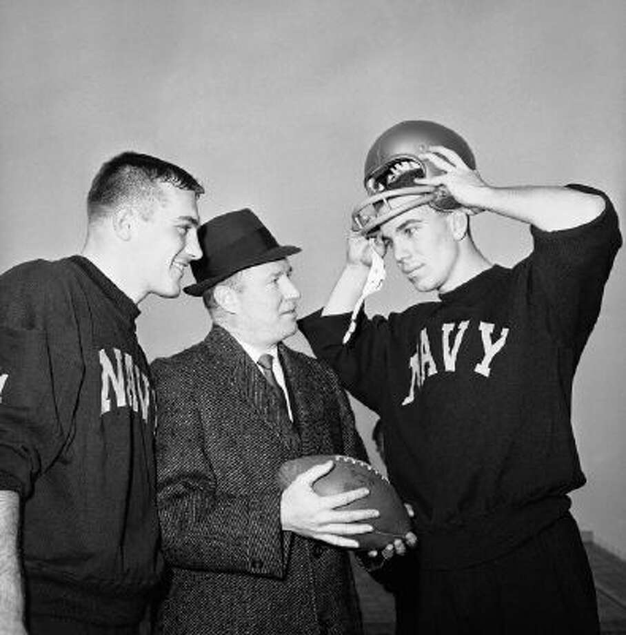 Navy coach Wayne Hardin, center, talks with his star quarterback, Roger Staubach, right, in final workout in Philadelphia Stadium on Dec. 7, 1963, before annual battle against Army, with center Tom Lynch listening in at left.
