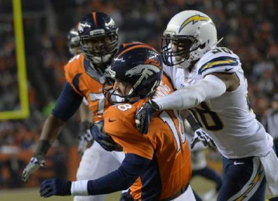 Denver Broncos quarterback Peyton Manning (18) gets sacked by San Diego Chargers strong safety Marcus Gilchrist (38) during the second quarter.