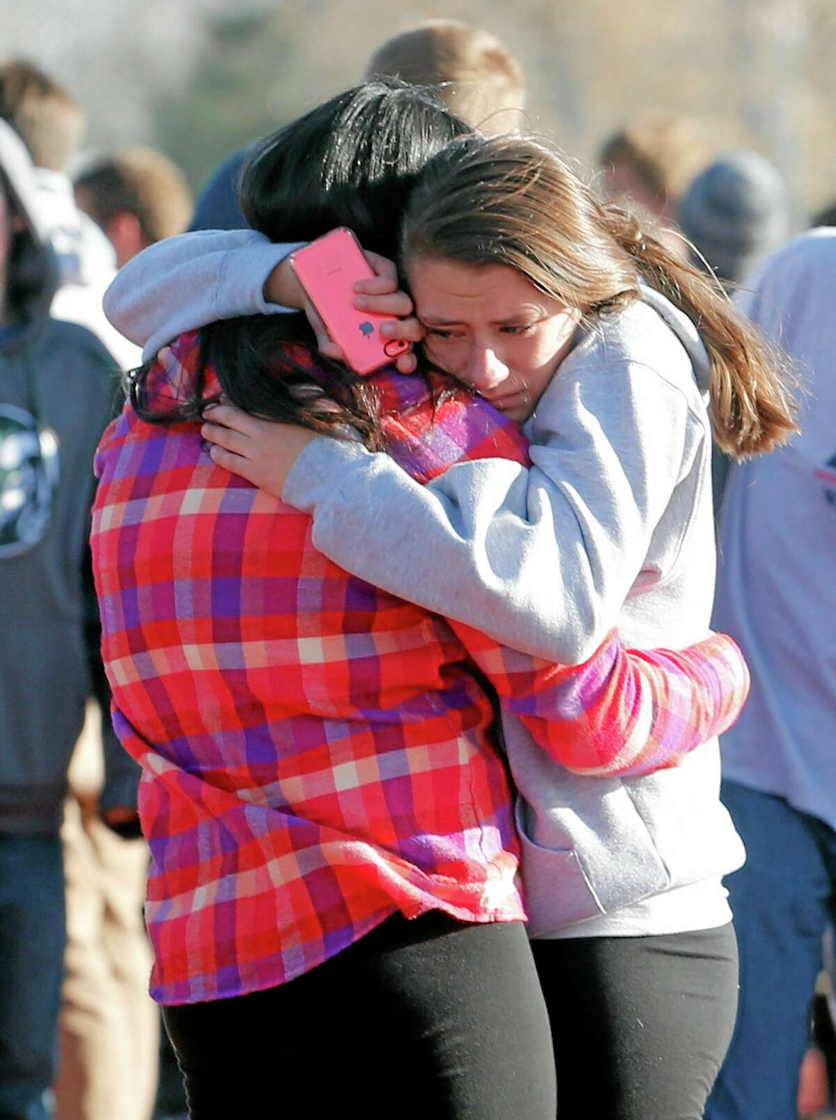 Students comfort each other outside Arapahoe High School in Centennial, Colo., Friday.