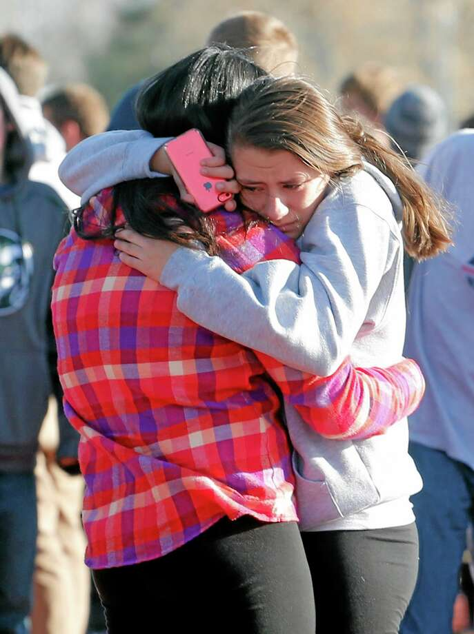Students comfort each other outside Arapahoe High School in Centennial, Colo., Friday. Photo: Ed Andrieski — The Associated PresS  / AP