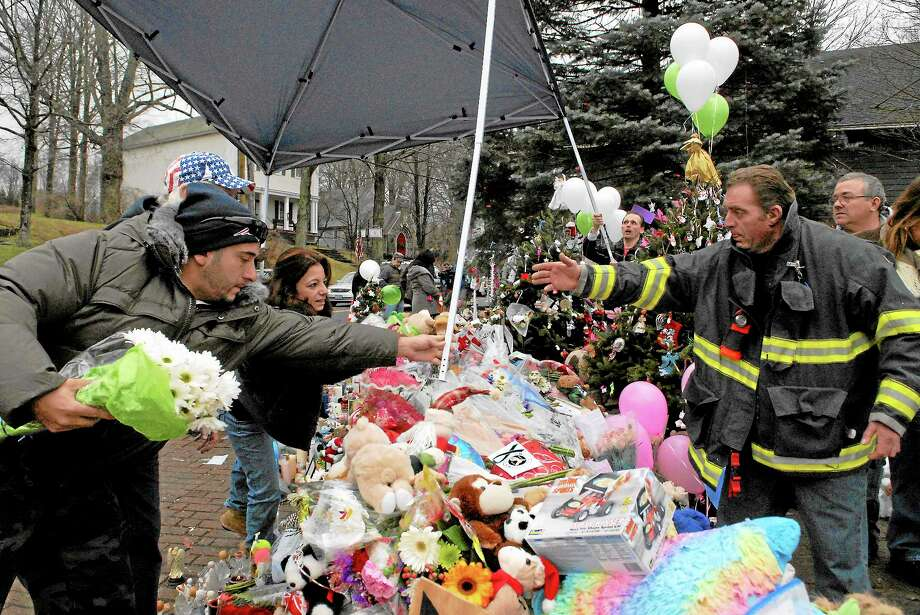 Members of the community set up a tent to keep the candles, flowers and teddybears dry at the memorial that was set up in the center of Sandy Hook after a fatal shooting killed 20 children and 6 adults at the Sandy Hook Elementary on Friday the 14th.Photo Erica Miller 12/18/12 Memorial7 Photo: Journal Register Co.