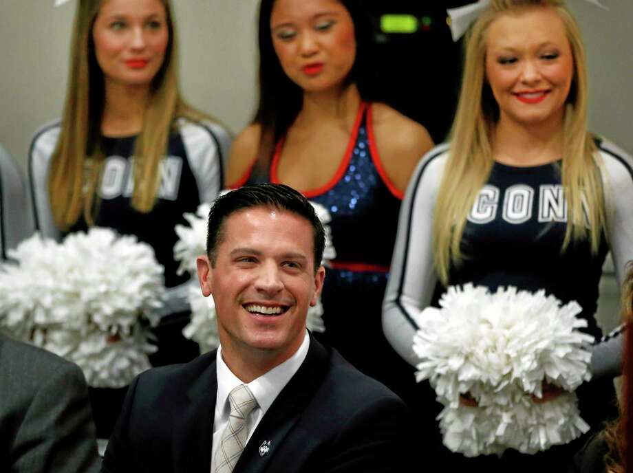 UConn cheerleaders stand behind Bob Diaco, former Notre Dame defensive coordinator, as he is introduced as the Huskies' new head football coach during a news conference in Storrs on Thursday. Photo: Elise Amendola — The Associated Press  / AP