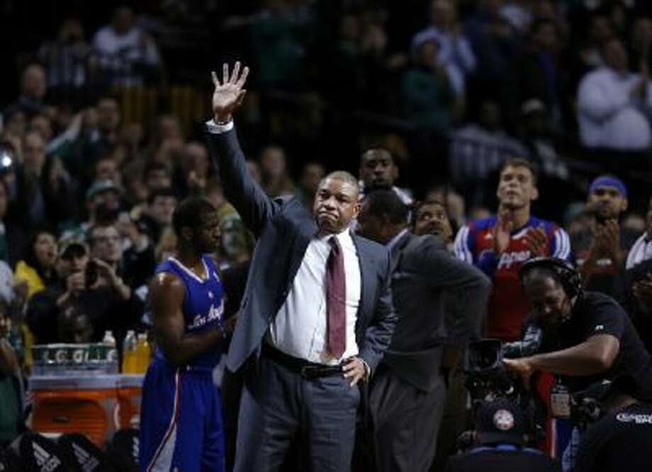 Doc Rivers waves after a video tribute to him was shown in his first time back to the TD Garden.
