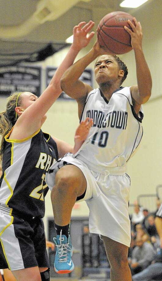 Middletown guard Rajeen Mayo elevates for a shot as RHAM's Marissa Catazaro defends during opening night at Sullivan-Labella Gymnasium at Middletown High School Wednesday night. RHAM won 65-50. Photo: Catherine Avalone — The Middletown Press  / TheMiddletownPress