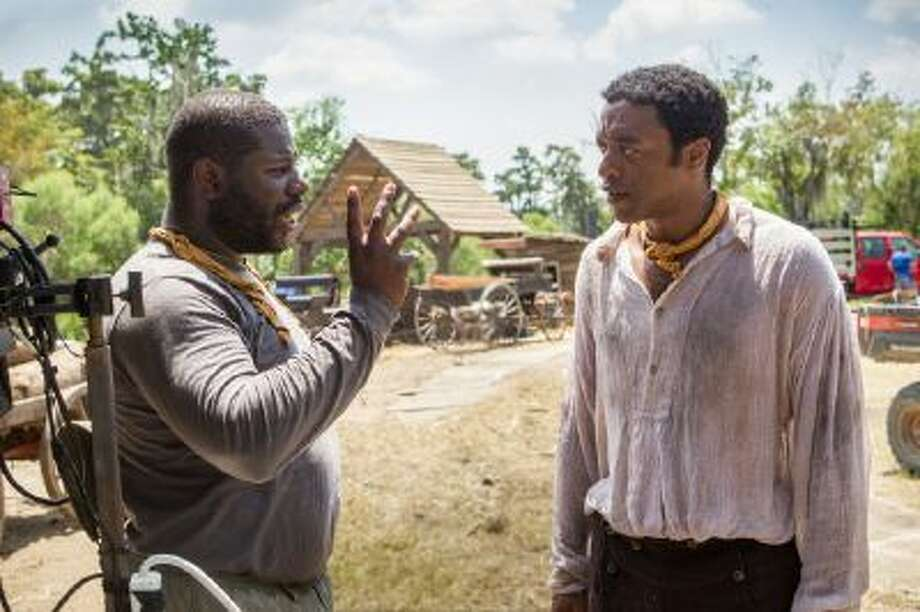 "This image released by Fox Searchlight shows director Steve McQueen, left, and actor Chiwetel Ejiofor during the filming of ""12 Years A Slave."""