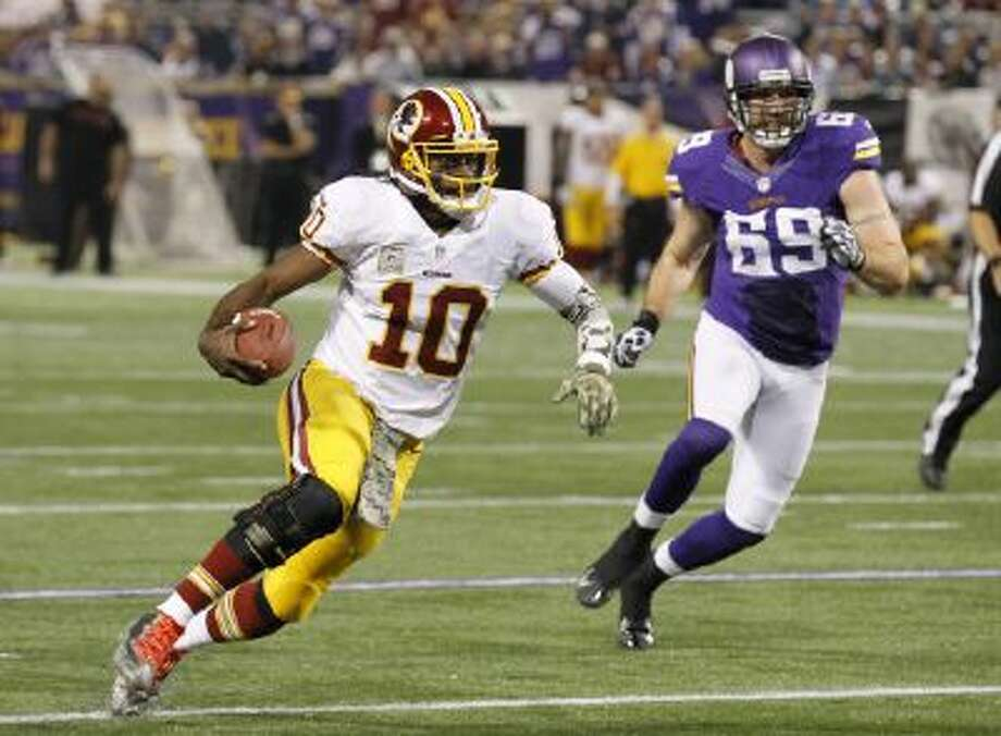 Washington Redskins quarterback Robert Griffin III runs from Minnesota Vikings defensive end Jared Allen (69) Thursday.