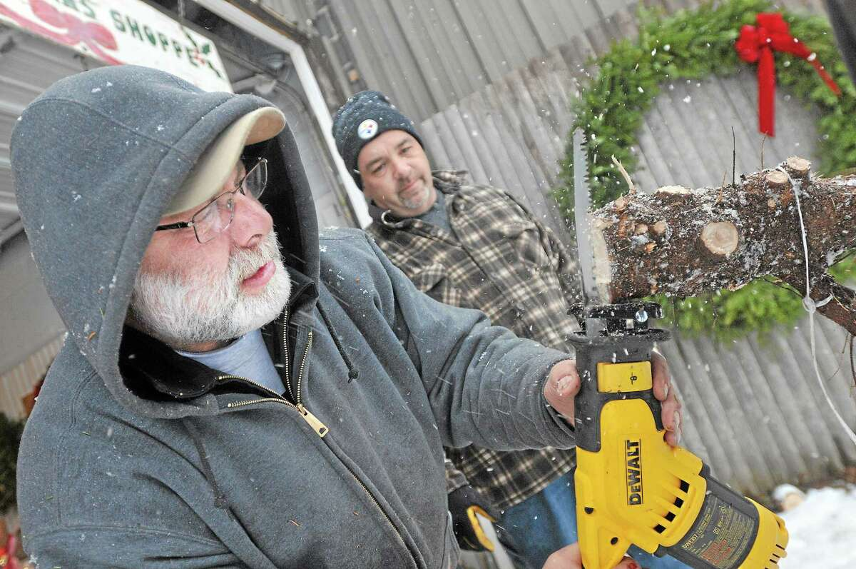 Bob Miller, co-owner of Miller Tree Farm in Durham uses a saw to cut an x into the bottom of a tree at the request of David Najam of Southington, at right. Najam believes the cut into the trunk helps the tree get water. Najam and his girlfriend, Christine Backstrom purchased the 8 foot tree for her home in Durham. Catherine Avalone - The Middletown Press