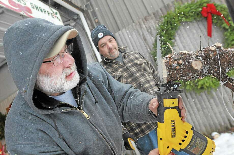 Bob Miller, co-owner of Miller Tree Farm in Durham uses a saw to cut an x into the bottom of a tree at the request of David Najam of Southington, at right. Najam believes the cut into the trunk helps the tree get water. Najam and his girlfriend, Christine Backstrom purchased the 8 foot tree for her home in Durham. Catherine Avalone - The Middletown Press Photo: Journal Register Co. / TheMiddletownPress