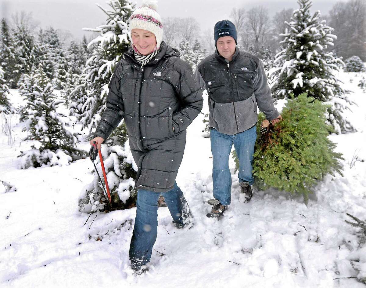 Wallingford resident Ewelina Karsky, who moved here from Poland 13 years ago, is happy that she and her husband Gregory found the perfect tree at Miller Tree Farm in Durham Tuesday afternoon. Catherine Avalone - The Middletown Press