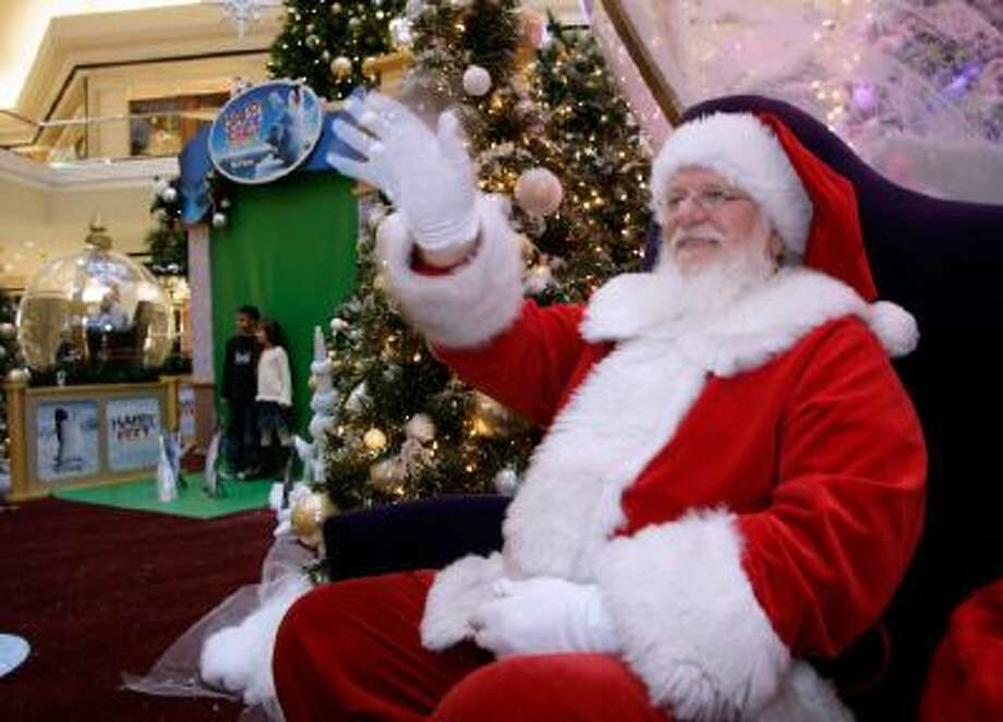A man dressed as Santa Claus waves to holiday well-wishers while waiting for children to visit his meeting place in the Cherry Creek Shopping Center in Denver.