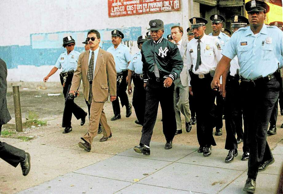 Police flank Nelson Mandela during an unannounced morning walk in Washington, D.C., in 1990. Mandela walked more than 20 blocks, wearing a New York Yankees cap and jacket. Photo: Jeff Markowitz — The Associated Press  / AP
