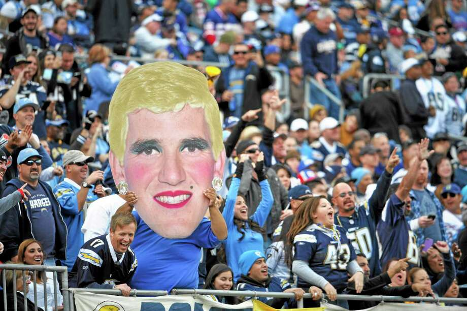 San Diego Chargers fans hold an altered image of New York Giants quarterback Eli Manning during Sunday's game in San Diego. Photo: Denis Poroy — The Associated Press  / FR59680 AP