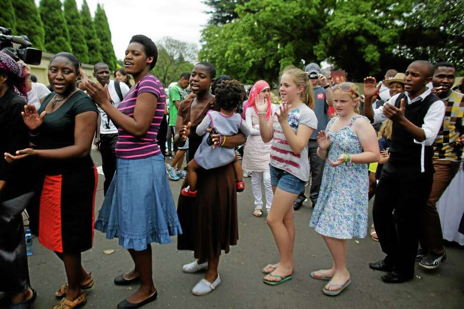 Black and White people dance together to celebrate the live of former South Africa President Nelson Mandela outside of his house in Johannesburg. AP Photo/Markus Schreiber Photo: AP / AP