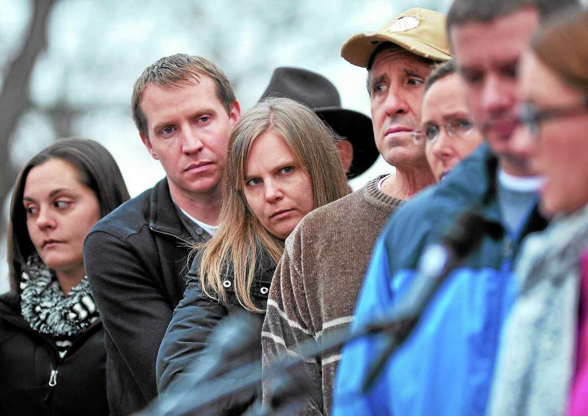 Parents and other family members of the victims of the Sandy Hook mass shooting listen to JoAnn Bacon, far right, mother of slain first-grader Charlotte Bacon, speak Monday in advance of the one-year mark since the Sandy Hook school shootings.