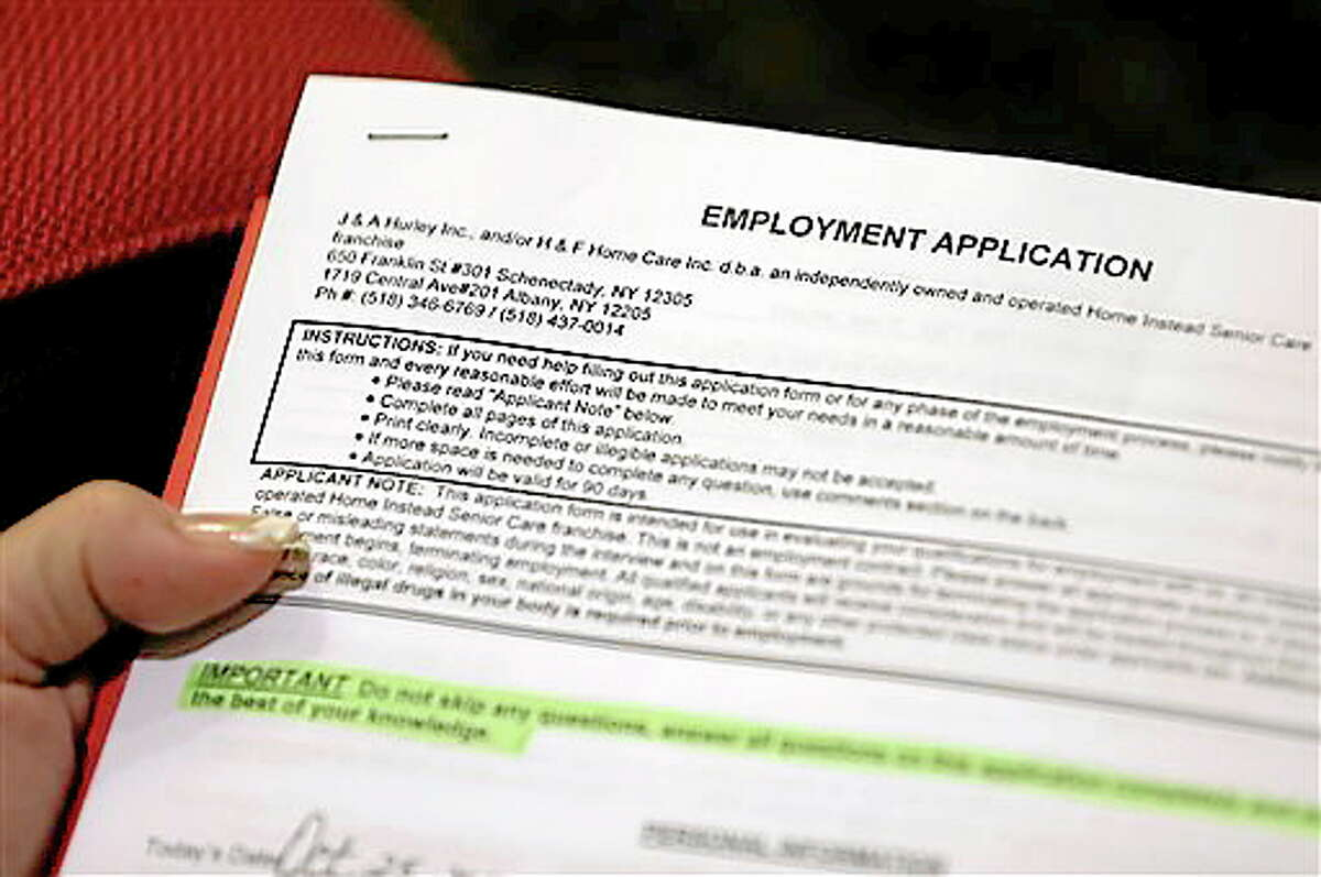In this Thursday, Oct. 25, 2012, photo, Carmen Nazario of Albany, N.Y., fills out an employment application during a job fair at the Marriott Hotel in Colonie, N.Y. The number of Americans seeking unemployment benefits fell 23,000 to a seasonally adjusted 393,000 for the last full week of November 2012. It was the second straight drop after Superstorm Sandy had driven applications much higher earlier in November (AP Photo/Mike Groll)