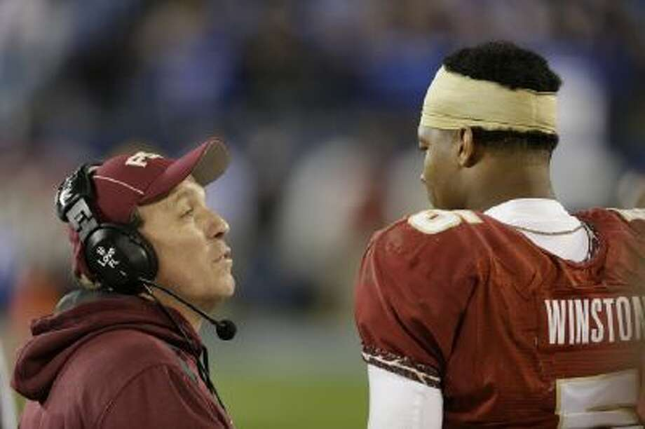 Florida State head coach Jimbo Fisher, left, talks with Jameis Winston, right, in the closing minutes of the Atlantic Coast Conference Championship NCAA football game against Duke in Charlotte, N.C., Saturday, Dec. 7, 2013. Florida State defeated Duke 45-7.