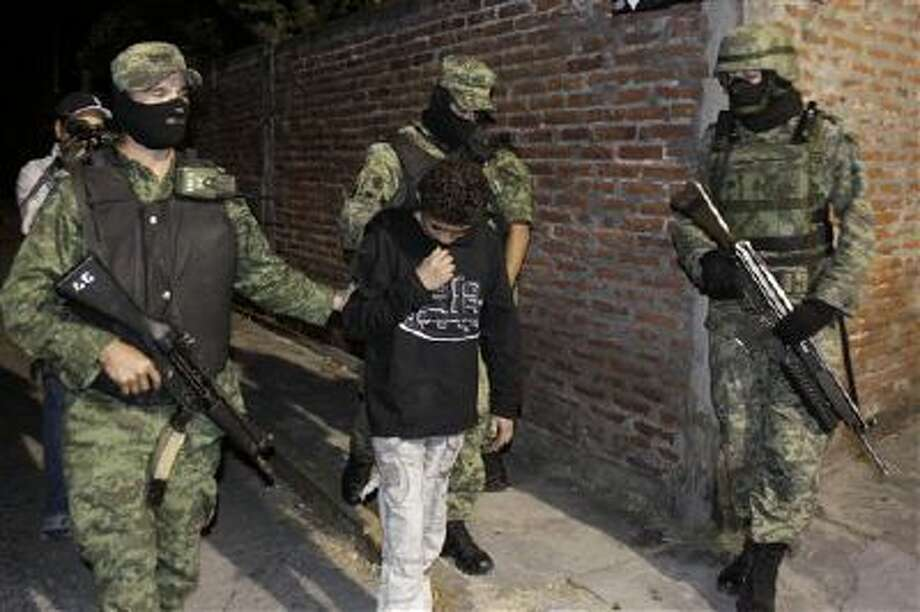 "Mexican soldiers present Edgar ""El Ponchis"" Jimenez Lugo to the media in the city of Cuernavaca, Mexico, in this 2010 file photo. The teenage U.S. citizen who acknowledged being a drug-cartel killer has finished his three-year juvenile-offender term for homicide, kidnapping and drug and weapons possession. The interior secretary of southern Morelos state says the teen was released and taken to an airport Nov. 26 to be sent to the United States, where he has family. Photo: AP / AP"