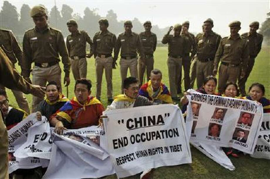 Indian policemen stand guard Monday as Tibetan exiles show slogans during a protest against the alleged human rights abuses of Tibetans by the Chinese government outside the Chinese embassy on the eve of World Human Rights Day in New Delhi, India. Tibetans also mark Dec. 10 as the Nobel peace Prize Day, the day their spiritual leader the Dalai Lama received the Nobel peace Prize in 1989. Photo: AP / AP