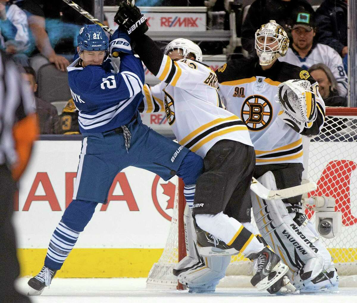 Boston Bruins goaltender Chad Johnson looks on as defenceman Matt Bartkowski tries to clear Toronto Maple Leafs left winger James van Riemsdyk (21) during the third period of an NHL hockey game in Toronto on Sunday, Dec. 8, 2013. (AP Photo/The Canadian Press, Frank Gunn)
