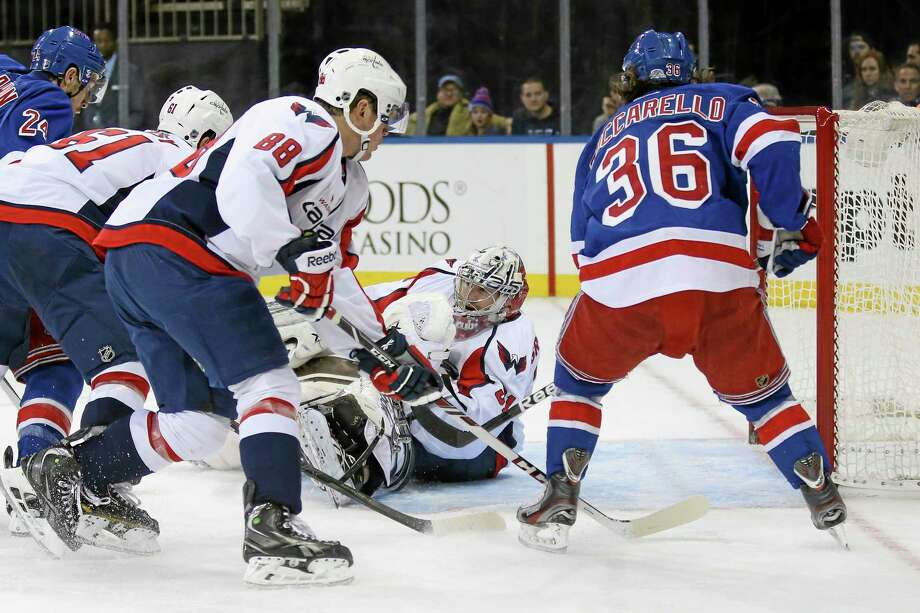 Washington Capitals goalie Philipp Grubauer (31), of Germany, makes a save as Steve Oleksy (61),  Nate Schmidt (88), and New York Rangers' Mats Zuccarello (36), of Norway, look on in the second period of an NHL hockey game on Sunday, Dec. 8, 2013, in New York. (AP Photo/John Minchillo) Photo: AP / FR170537 AP
