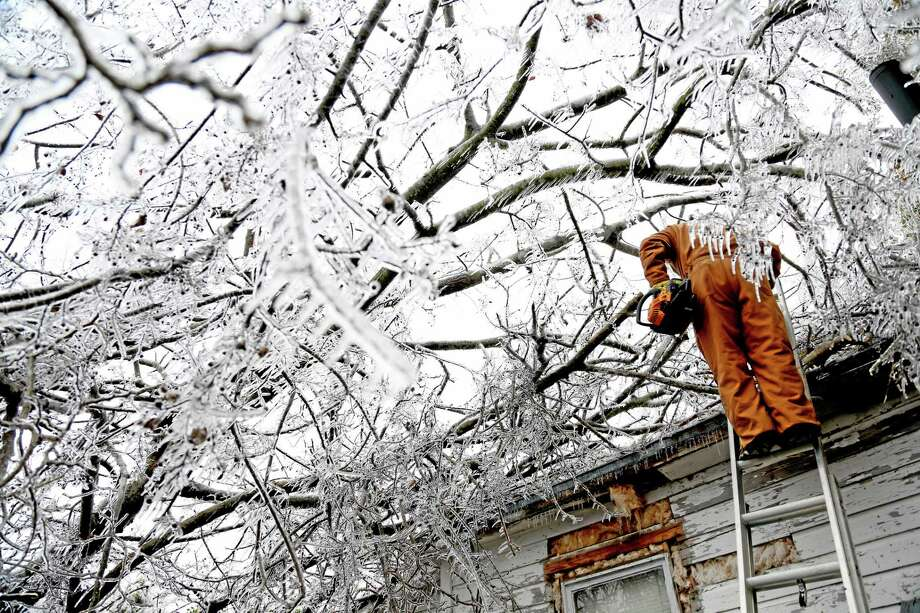 Randy Dean carries a chainsaw down from his roof in Paris, Texas, Saturday, Dec. 7, 2013. Electrical crews are coming into North East Texas from all over to help restore power to thousands of residents that lost it when an ice storm caused trees and branches to snap pulling down lines and blowing up transformers. (AP Photo/The Paris News, Sam Craft) MANDATORY CREDIT Photo: AP / The Paris News