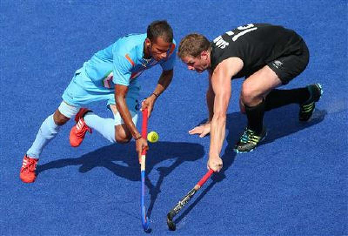 New Zealand's Bradley Shaw, right, and India's SV Sunil vie for the ball during their men's hockey preliminary round match at the 2012 Summer Olympics, Wednesday, Aug. 1, 2012, in London.