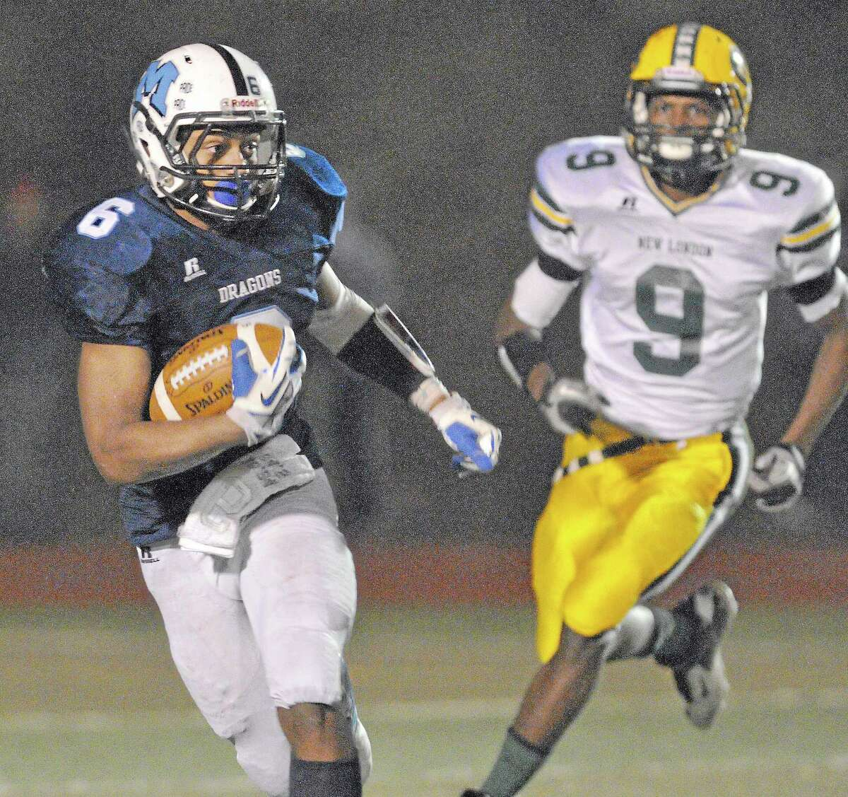 Middletown junior quarterback Dario R. Highsmith, Jr. clears New London's Tremell Scott in the CIAC Class L quarterfinal game Tuesday night at Rosek-Skubel Stadium at MHS. The Middletown Blue Dragons defeated the New London Whalers 49-14. Number 4 Middletown (11-1) will play #1 Darien (11-1) Saturday at Pomperaug. Catherine Avalone - The Middletown Press