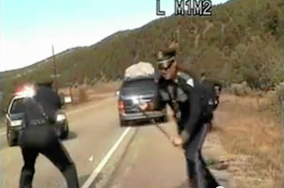 Three New Mexico State Police officers react as a minivan driven by motorist Oriana Farrell pulls away from a chaotic traffic stop that included one officer bashing the van's window with his night stick and another, Elias Montoya, at left, firing three shots as the van drives off, in this video made Oct. 28, from the dashboard camera of the police cruiser. Montoya, the officer who fired at the van full of children, has been suspended. (AP Photo/New Mexico State Police) Photo: AP / New Mexico State Police