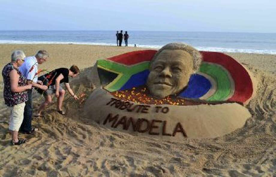 Tourists offer floral tributes near a sand sculpture of Nelson Mandela on a beach in Puri, India, Friday, Dec. 6, 2013.