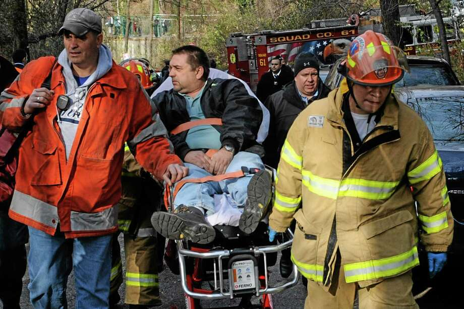 FILE - In this file photo taken on Sunday, Dec. 1, 2013, Metro North Railroad engineer William Rockefeller is wheeled on a stretcher away from the area where the commuter train he was operating derailed in the Bronx borough of New York. The engineer driving the commuter train that went off the rails in New York City last weekend has been suspended without pay according to a spokesman for Metro-North Railroad Thursday Dec. 5, 2013. (AP Photo/Robert Stolarik, File) Photo: AP / AP