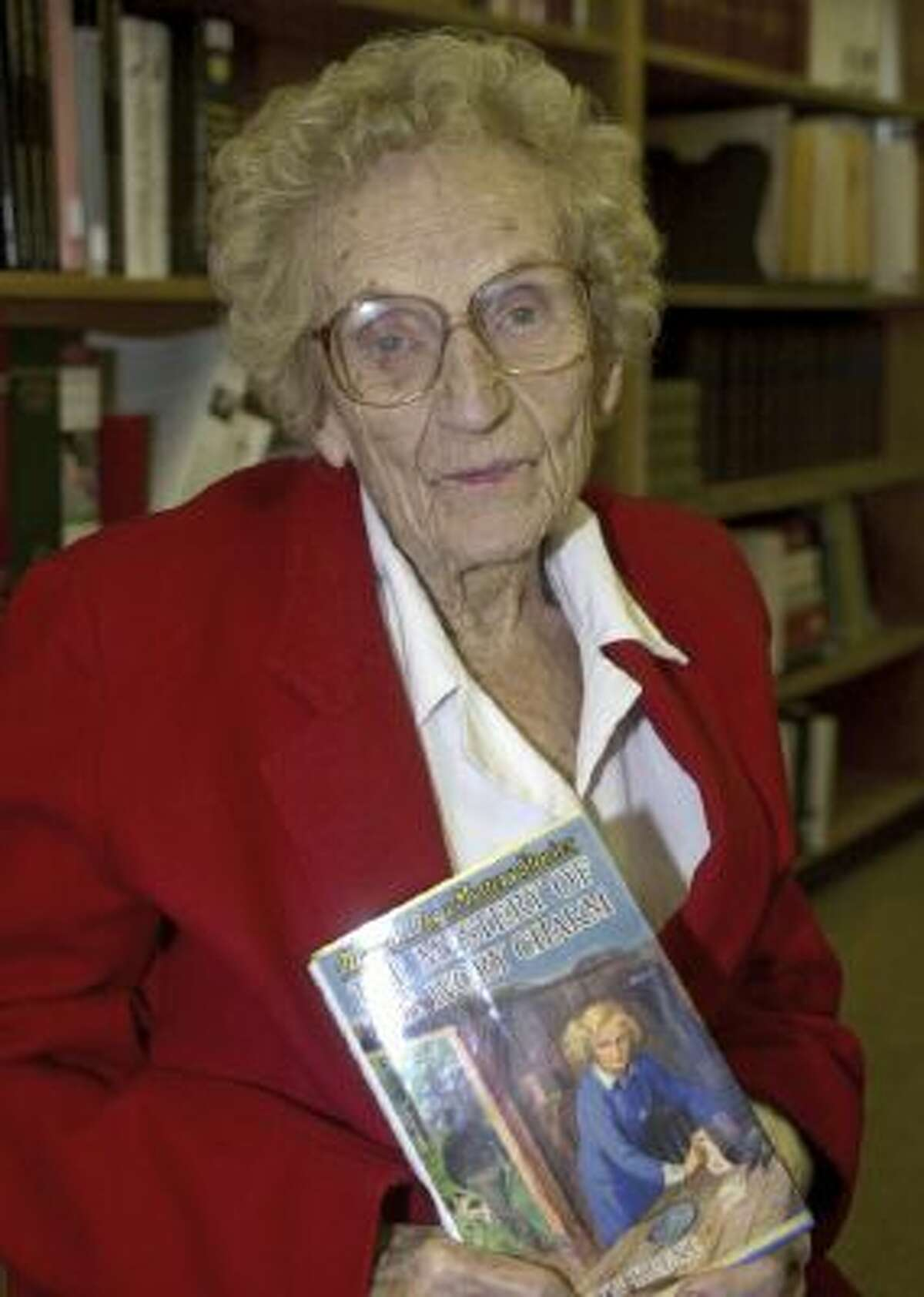 In this Tuesday, Dec. 18, 2001 file photo shows Millie Benson holding up one of the Nancy Drew mystery books in Toledo, Ohio.