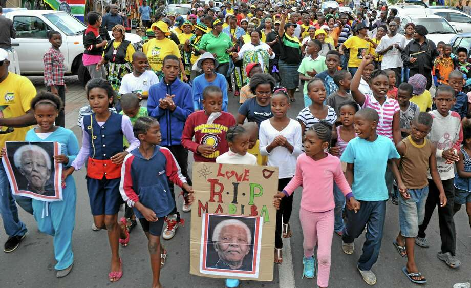 """Children with placards showing the face of Nelson Mandela and referring to his clan name """"Madiba"""", march  to celebrate his life, in the street outside his old house in Soweto, Johannesburg, South Africa Friday, Dec. 6, 2013. Flags were lowered to half-staff and people in black townships, in upscale mostly white suburbs and in South Africa's vast rural grasslands commemorated Nelson Mandela with song, tears and prayers on Friday while pledging to adhere to the values of unity and democracy that he embodied. (AP Photo/Athol Moralee) Photo: AP / AP"""