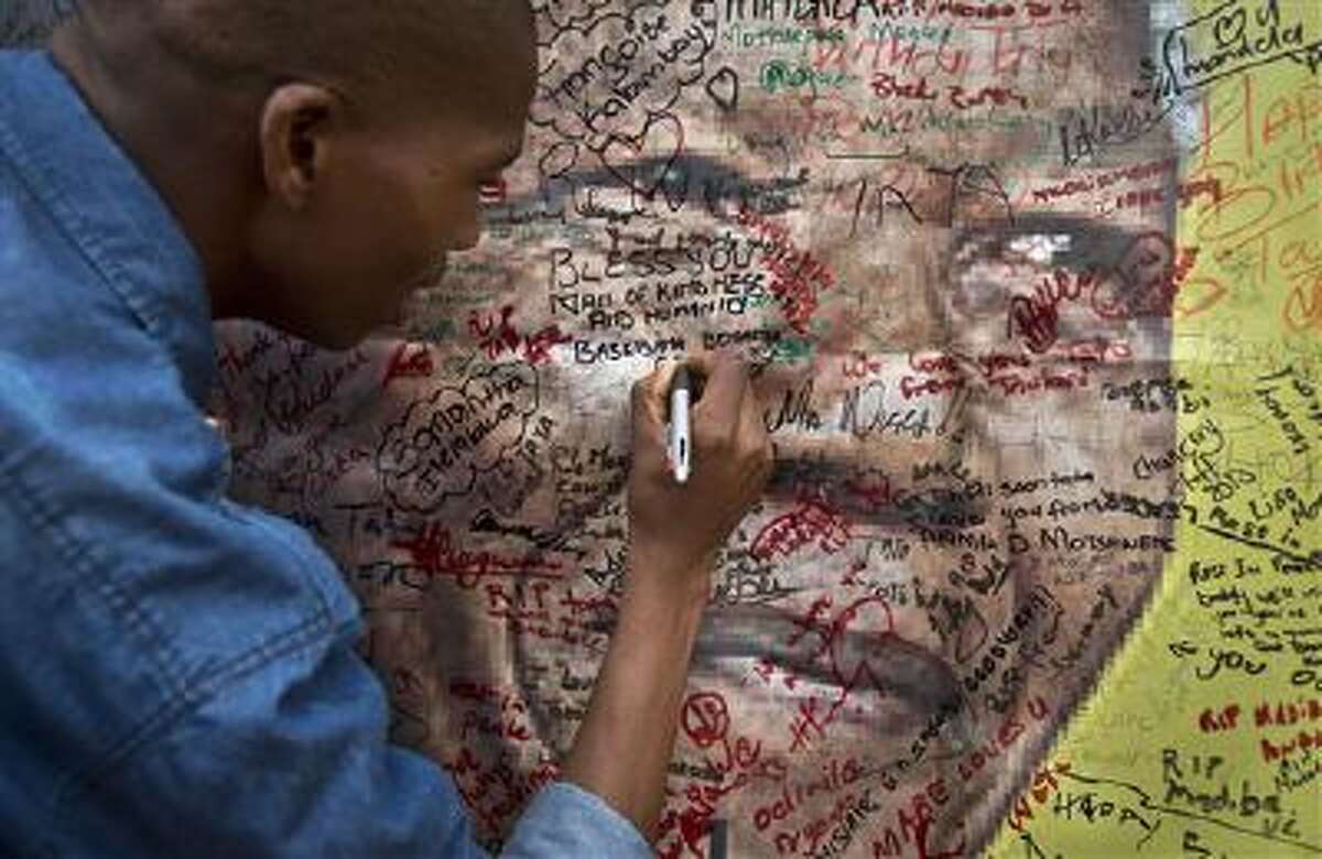 A message is written on a poster of Nelson Mandela outside his old house in Soweto, Johannesburg, on Friday.