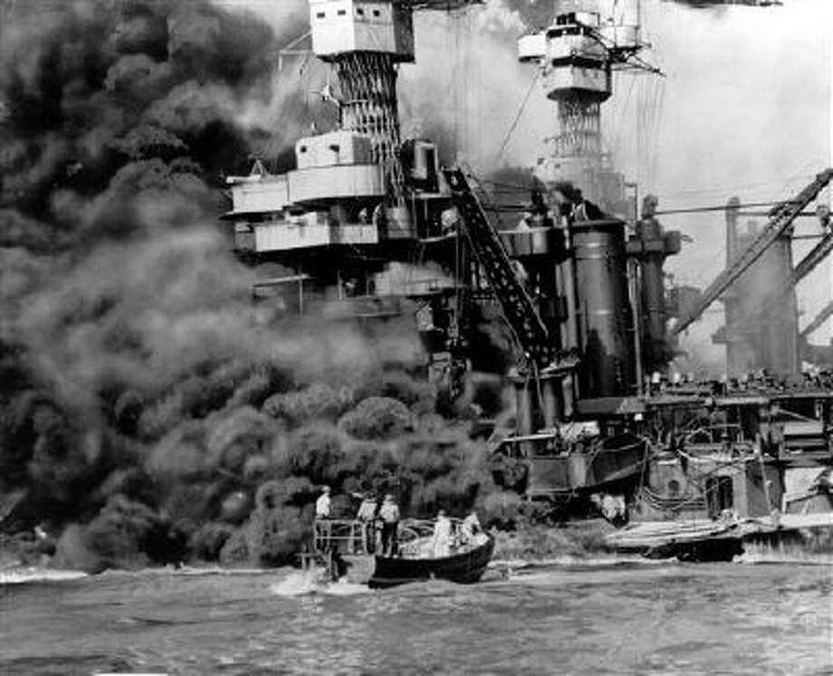 A small boat rescues a crew member from the water as heavy smoke rolls out of the stricken USS West Virginia after the Japanese bombing of Pearl Harbor, Hawaii, on Dec. 7, 1941. Two men can be seen on the superstructure, upper center. The mast of the USS Tennessee is beyond the burning West Virginia. Saturday marks the 72nd anniversary of the attack that brought the United States into World War II. Photo: AP / AP