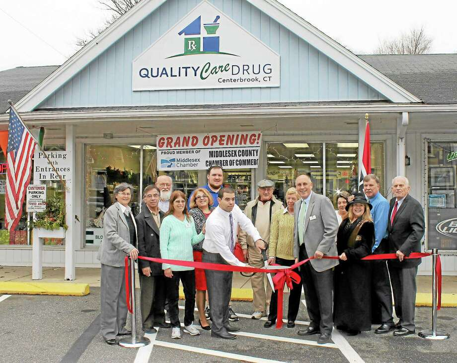 Chamber Chairwoman Darlene Briggs and President Larry McHugh help Pharmacist/Owner Greg McKenna (center, jacket and tie) and his team cut the ribbon at Quality Care Drug in Essex. Photo: Submitted Photo