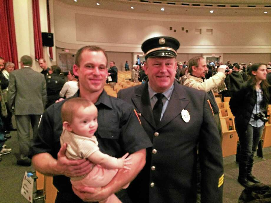 Fire academy graduate Christopher J. Guilfoil, 28, of East Haven, is photographed with his daughter, Olivia, 8 months, and his father, John M. Guilfoil Jr. The younger Guilfoil will work with the East Haven Fire Department, where his father has served for many years. The graduate also is a paramedic who worked for American Medical Response before joining the fire department. Photo: CONTRIBUTED PHOTO