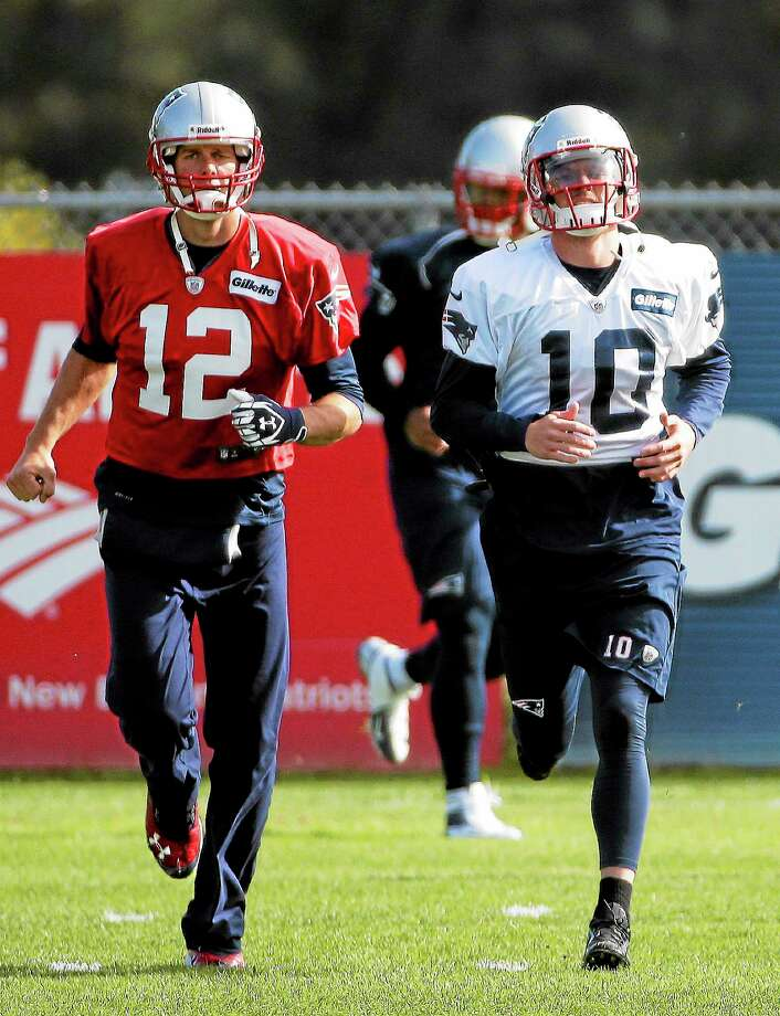 New England Patriots quarterback Tom Brady (12) and then-newly acquired receiver Austin Collie (10) run during practice at the team's facility in Foxborough, Mass., on Oct. 9. After letting him go, the Patriots have signed Collie again. Photo: Stephan Savoia — The Associated Press  / AP