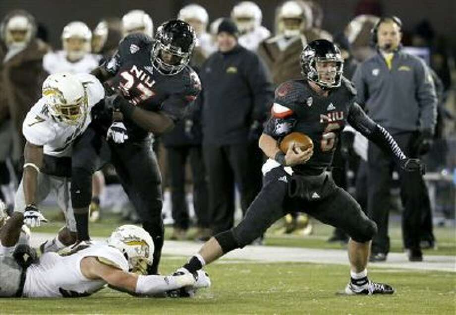 Northern Illinois quarterback Jordan Lynch carries the ball past several Western Michigan defenders during the second half of an NCAA football game Tuesday, Nov. 26, 2013, in DeKalb, Ill. Northern Illinois won 33-14. Photo: AP / AP