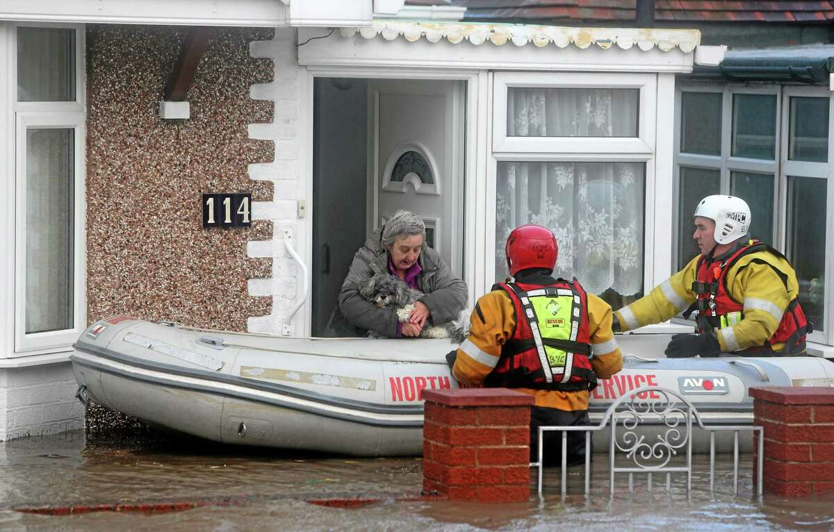 A woman and her dog are rescued by the RNLI or Royal National Lifeboat Institute, from floods as heavy seas and high tides sweep across the country, in Rhyl, Wales, Thursday Dec. 5, 2013. Gale-force winds hit Scotland on Thursday, causing a fatal truck accident, halting all trains and leaving tens of thousands of homes without electricity as much of northwestern Europe braced for a storm that was expected to bring flooding to coastal areas. (AP Photo/PA, Peter Byrne)