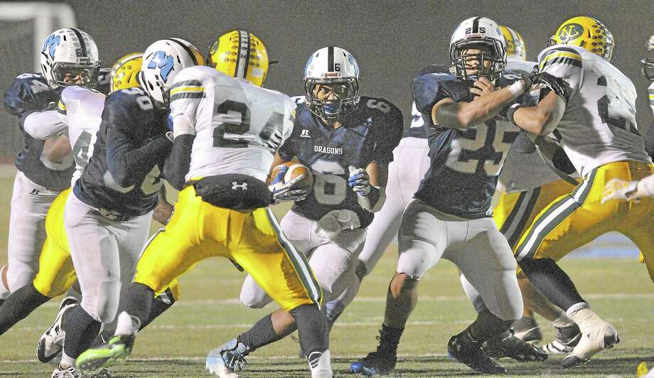 Middletown junior quarterback Dario R. Highsmith Jr. plows through the New London as teammates senior Julian Carraway (30) and junior running back Isaiah Thompkins (25) defend in a Class L quarterfinal game Tuesday night. Middletown defeated New London 49-14. Photo: Catherine Avalone - The Middletown Press  / TheMiddletownPress
