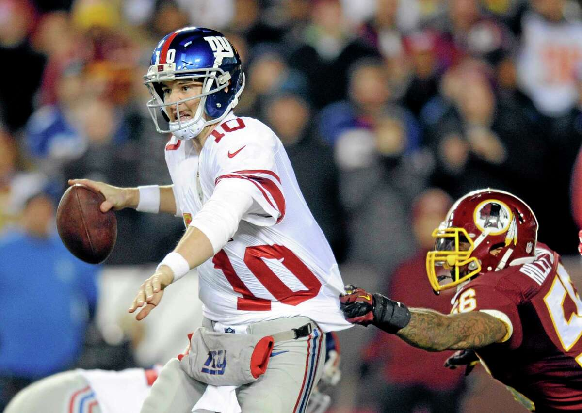 New York Giants quarterback Eli Manning (10) looks to pass as Washington Redskins inside linebacker Perry Riley hangs onto his jersey during Sunday's game in Landover, Md.