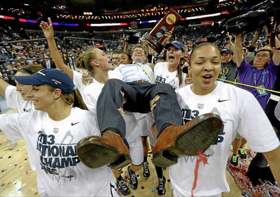 FOR USE AS DESIRED, YEAR END PHOTOS - FILE - Connecticut players celebrate as they carry their head coach Geno Auriemma after defeating Louisville 93-60 in the national championship game of the women's Final Four of the NCAA college basketball tournament, Tuesday, April 9, 2013, in New Orleans. (AP Photo/Dave Martin, File) Photo: AP / AP