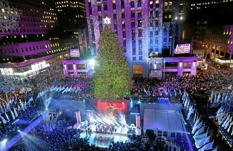 The Rockefeller Center Christmas tree is lit during a ceremony, Wednesday, Dec. 4, 2013, in New York. Some 45,000 energy efficient LED lights adorn the 76-foot tree. (AP Photo/Kathy Willens) Photo: AP / AP