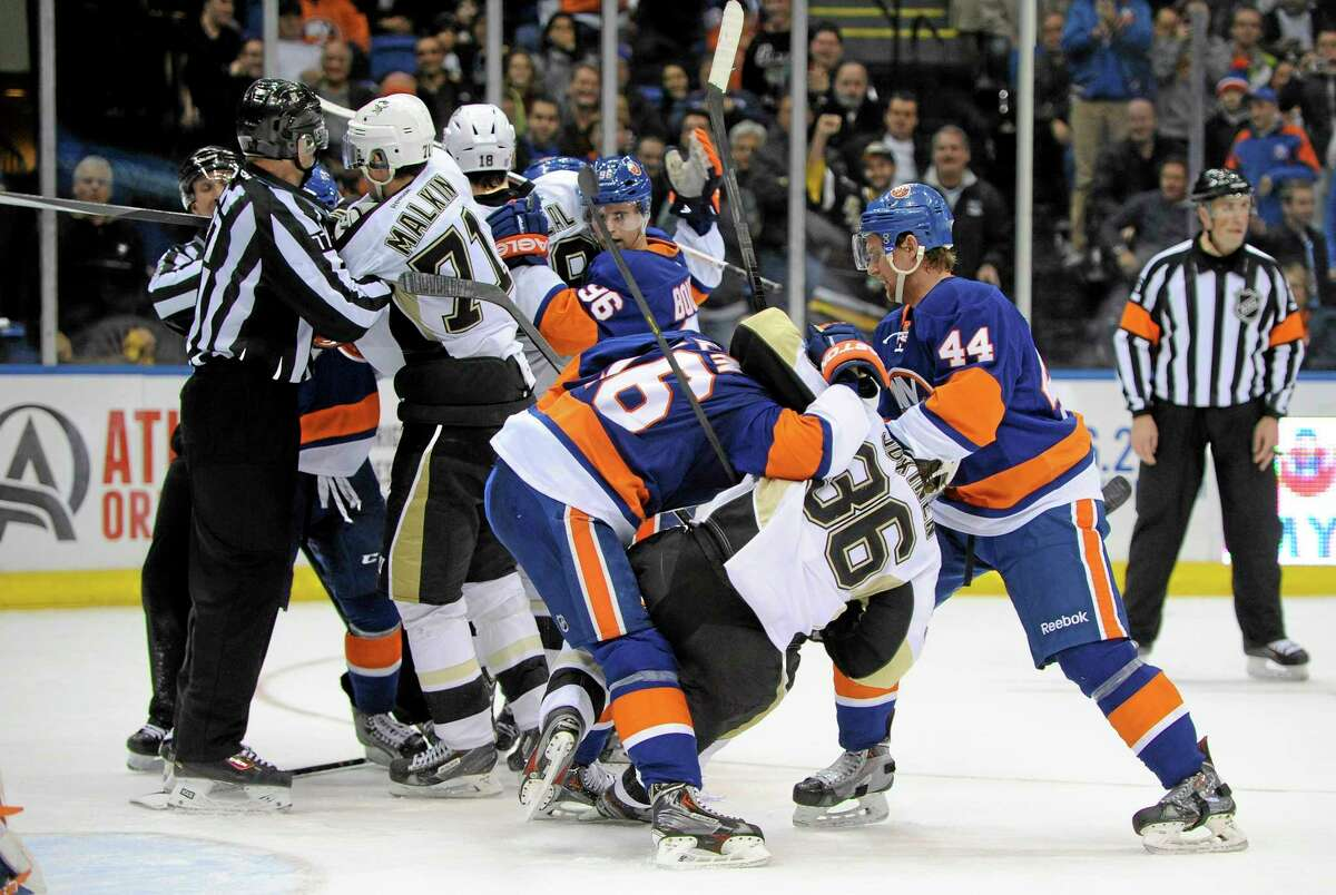 The Penguins' Evgeni Malkin (71), Jussi Jokinen (36) and teammates fight with the Islanders' Peter Regin (16), Calvin de Haan (44) and teammates during the third period of Tuesday's game in Uniondale, N.Y. Pittsburgh beat New York 3-2 in overtime.
