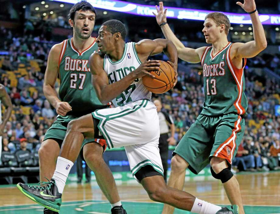 Celtics guard Jordan Crawford drives against Milwaukee Bucks center Zaza Pachulia (27) and point guard Luke Ridnour (13) in the first half of Tuesday's game in Boston. Crawford led all scorers with 25 points as the Celtics beat the Bucks 108-100. Photo: Elise Amendola — The Associated Press  / AP